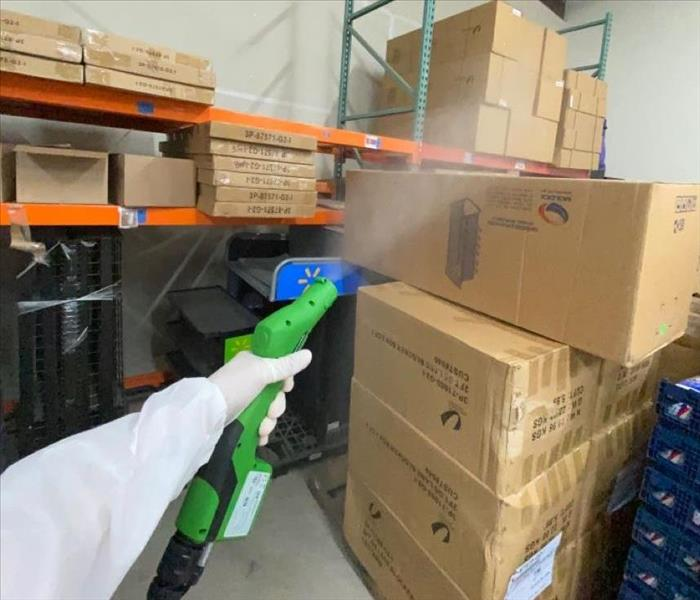 man in PPE spraying building with green sprayer