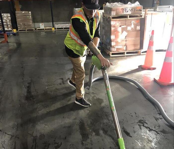 Male employee extracting water from a warehouse floor