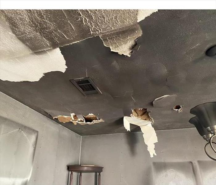 Home with soot and smoke damage with ceiling peeling off.
